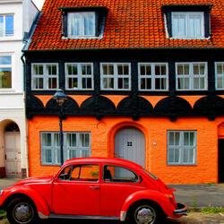 Пазл онлайн: Красный автомобиль перед оранжевым домом
